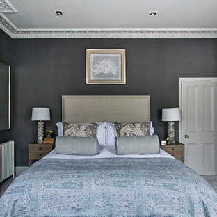 Photo of a traditional bedroom with black walls, carpet, a standard fireplace and grey floors.