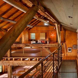Diseño de dormitorio tipo loft, rural, con suelo de madera en tonos medios