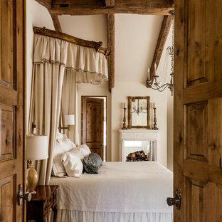 Пример оригинального дизайна: спальня в средиземноморском стиле с бежевыми стенами и двусторонним камином