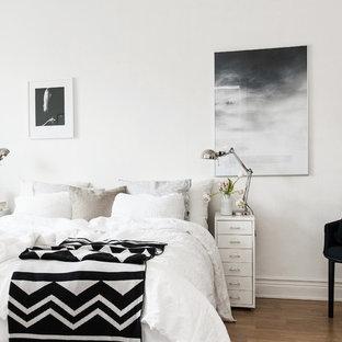 Cette photo montre une chambre parentale scandinave de taille moyenne avec un mur blanc, un sol en bois brun et aucune cheminée.