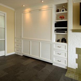 Imagen de habitación de invitados tradicional renovada, de tamaño medio, con paredes beige, suelo de pizarra, chimenea tradicional, marco de chimenea de yeso y suelo negro