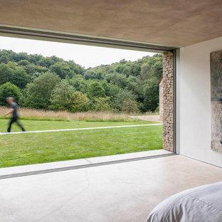 Imagen de dormitorio moderno con suelo de cemento