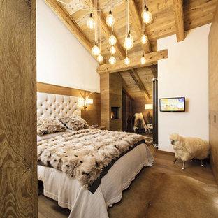 Идея дизайна: маленькая хозяйская спальня в стиле рустика с белыми стенами, паркетным полом среднего тона, коричневым полом, подвесным камином и фасадом камина из дерева