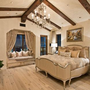 Exemple d'une chambre parentale méditerranéenne avec un mur beige, un sol en bois clair et une cheminée standard.