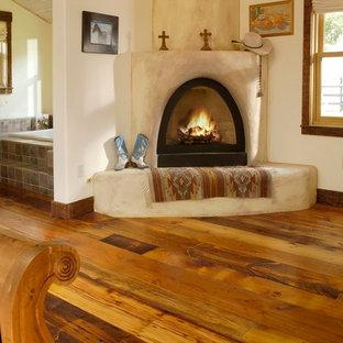 デンバーの巨大なラスティックスタイルのおしゃれな主寝室 (白い壁、無垢フローリング、漆喰の暖炉まわり、コーナー設置型暖炉)