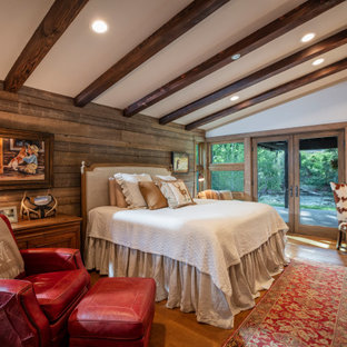 Rustikales Schlafzimmer mit weißer Wandfarbe, braunem Holzboden, Kamin, Kaminumrandung aus gestapelten Steinen, braunem Boden, freigelegten Dachbalken, gewölbter Decke und Holzwänden in Denver