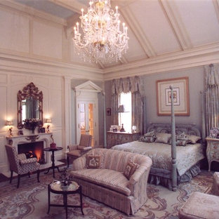 Modelo de dormitorio principal, clásico, grande, con paredes azules, suelo de madera oscura, chimenea tradicional, marco de chimenea de piedra y suelo beige