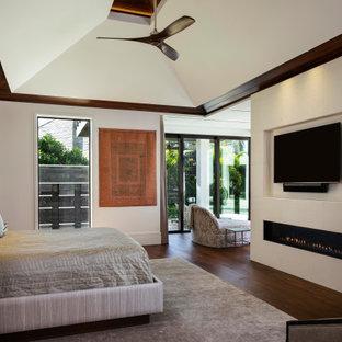 広い地中海スタイルのおしゃれな主寝室 (白い壁、無垢フローリング、標準型暖炉、タイルの暖炉まわり、三角天井、板張り壁) のレイアウト