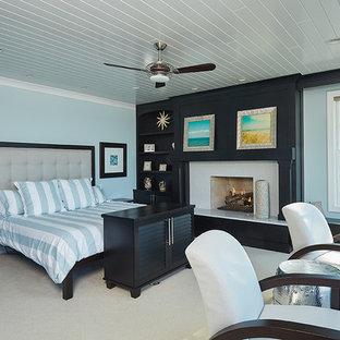 Foto de dormitorio principal, tradicional, grande, con paredes azules, moqueta, chimenea tradicional, marco de chimenea de hormigón y suelo beige