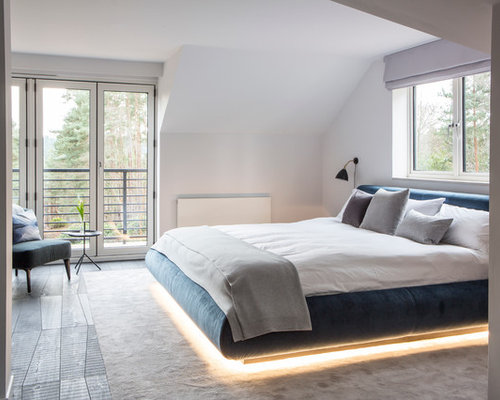 under furniture lighting. example of a trendy bedroom design in sussex with white walls under furniture lighting