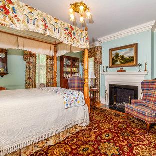 Ejemplo de dormitorio principal, grande, con paredes verdes, moqueta, chimenea tradicional, marco de chimenea de baldosas y/o azulejos y suelo rojo