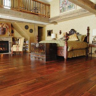 Imagen de dormitorio principal, clásico, grande, con paredes blancas, suelo de madera en tonos medios, chimenea tradicional y marco de chimenea de ladrillo