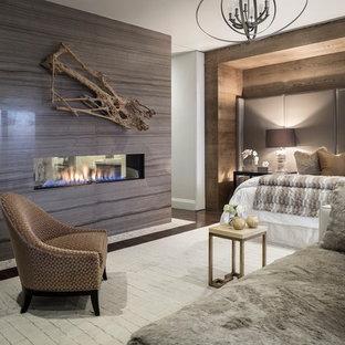 他の地域のコンテンポラリースタイルのおしゃれな主寝室 (濃色無垢フローリング、両方向型暖炉、タイルの暖炉まわり)
