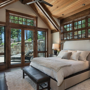 Photo of a large country master bedroom in Sacramento with white walls, dark hardwood floors, a standard fireplace, a stone fireplace surround and brown floor.