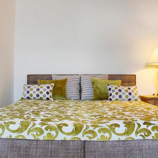 Foto de habitación de invitados contemporánea, de tamaño medio, sin chimenea, con paredes púrpuras y suelo de madera clara