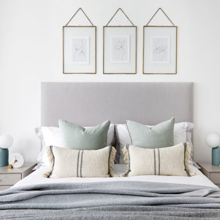 Inspiration for a scandinavian bedroom in London with white walls, medium hardwood flooring and brown floors.