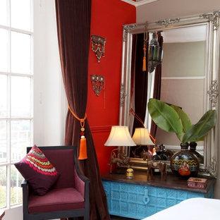 Immagine di una grande camera matrimoniale etnica con pareti rosse e moquette