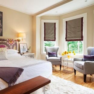 Foto di una camera da letto vittoriana con pareti beige e pavimento in legno massello medio