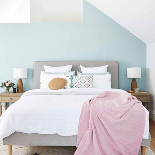Inspiration for a transitional master bedroom in Sydney with blue walls and light hardwood floors.