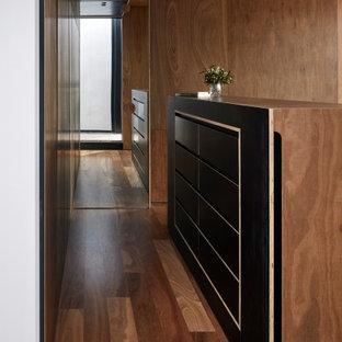 Modern inredning av ett mellanstort huvudsovrum, med bruna väggar, mellanmörkt trägolv och brunt golv