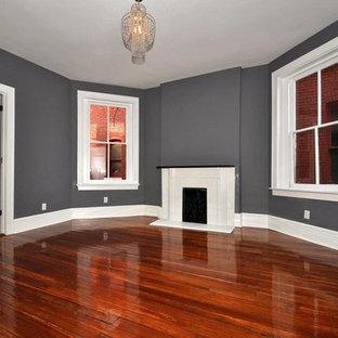 Foto de dormitorio principal, de estilo americano, de tamaño medio, con paredes grises, suelo de madera en tonos medios, chimenea tradicional, marco de chimenea de hormigón y suelo marrón