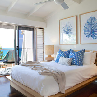 This is an example of a beach style master bedroom in Sunshine Coast with beige walls, dark hardwood floors and brown floor.
