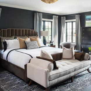 Modelo de dormitorio principal, tradicional renovado, extra grande, sin chimenea, con paredes negras, suelo de madera oscura y suelo marrón
