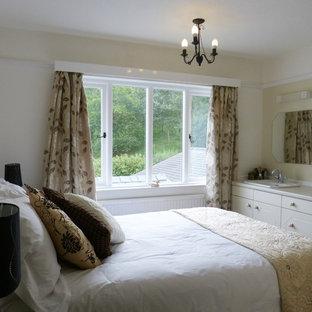 На фото: маленькая спальня в стиле фьюжн с бежевыми стенами, светлым паркетным полом, печью-буржуйкой и фасадом камина из камня с