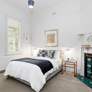 Transitional bedroom in Melbourne with white walls, carpet, a corner fireplace, a tile fireplace surround and grey floor.