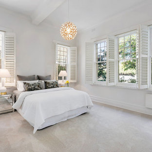 Photo of a large transitional master bedroom in Melbourne with white walls, carpet, no fireplace and beige floor.