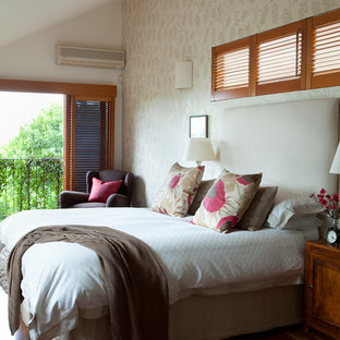 This is an example of a large beach style master bedroom in Brisbane with white walls and medium hardwood floors.