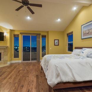 Foto de dormitorio principal, mediterráneo, de tamaño medio, con paredes amarillas, suelo de madera en tonos medios, chimenea tradicional y marco de chimenea de piedra