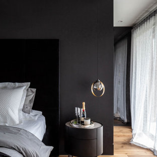 Inspiration for a contemporary bedroom in Sydney with black walls, medium hardwood floors and brown floor.