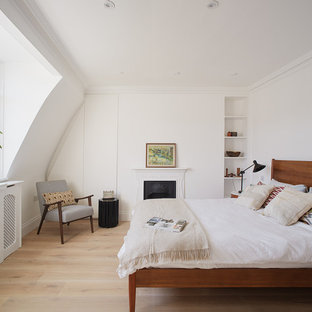 Design ideas for a scandinavian master bedroom in London with white walls, light hardwood flooring and no fireplace.