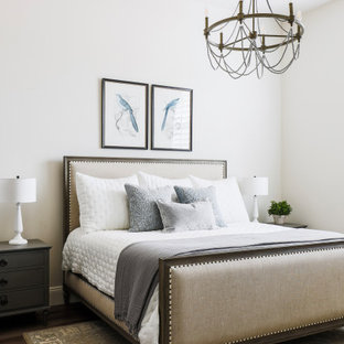 This is an example of a mid-sized mediterranean guest bedroom in Phoenix with medium hardwood floors, white walls and brown floor.