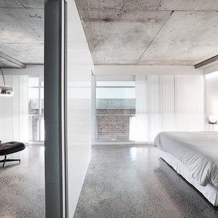 Foto de dormitorio actual con paredes blancas, suelo de cemento y suelo gris