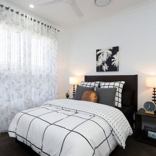 This is an example of a modern guest bedroom in Brisbane with white walls, carpet and black floor.