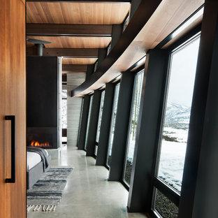 Свежая идея для дизайна: большая хозяйская спальня в современном стиле с бетонным полом, горизонтальным камином, фасадом камина из металла и серым полом - отличное фото интерьера
