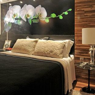 Esempio di una camera da letto contemporanea con pareti nere e pavimento in legno massello medio