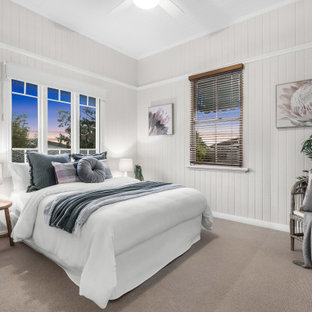 Design ideas for a beach style bedroom in Brisbane with planked wall panelling and timber.