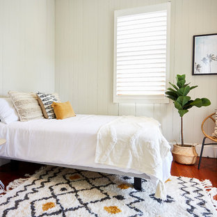 Inspiration for a large beach style guest bedroom in Townsville with white walls, medium hardwood floors and brown floor.