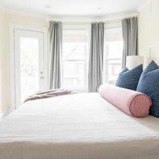 Ejemplo de dormitorio principal, tradicional renovado, pequeño, con paredes amarillas, suelo de madera clara y suelo marrón