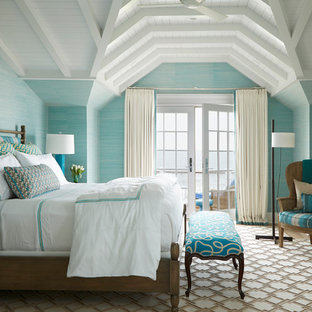 This is an example of a large beach style master bedroom in New York with blue walls, carpet and no fireplace.
