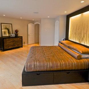 Foto de dormitorio principal, actual, grande, con paredes beige, suelo de madera clara, chimenea de esquina y marco de chimenea de metal