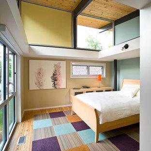 Mittelgroßes Modernes Gästezimmer ohne Kamin mit blauer Wandfarbe, braunem Holzboden und buntem Boden in Atlanta