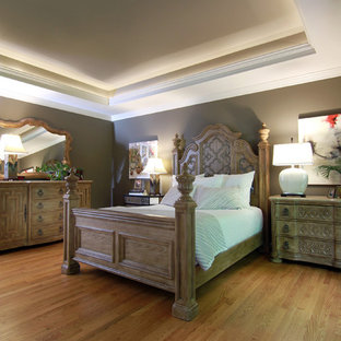 Example of a mid-sized transitional master medium tone wood floor bedroom design in Other with gray walls, a standard fireplace and a wood fireplace surround