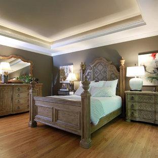 Immagine di una camera matrimoniale chic di medie dimensioni con pareti grigie, pavimento in legno massello medio, camino classico e cornice del camino in legno