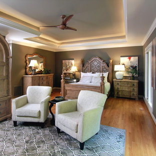 Example of a mid-sized transitional master medium tone wood floor bedroom design in Other with gray walls