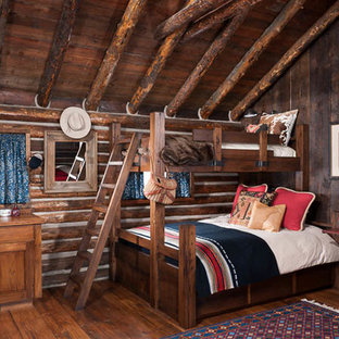 This is an example of a small country guest bedroom in Other with brown walls and medium hardwood floors.