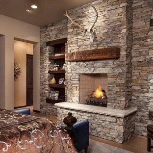Großes Mediterranes Hauptschlafzimmer mit beiger Wandfarbe, Betonboden, Kamin und Kaminumrandung aus Stein in Phoenix